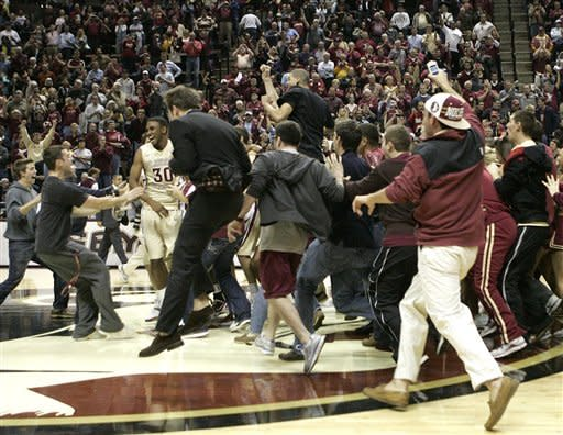 fans storm the floor after Florida State's 90-57 win No. 3 North Carolina in an NCAA college basketball game, Saturday, Jan. 14, 2012 in Tallahassee, Fla.(AP Photo/Steve Cannon)