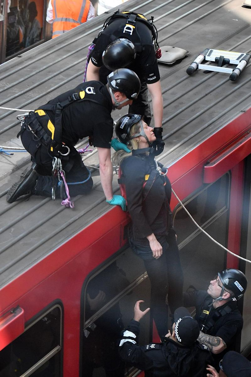 A climate protester is removed from the top of the DLR train (AFP/Getty Images)