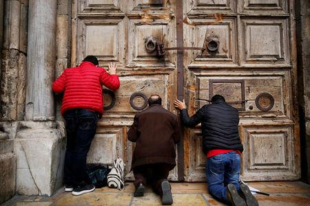 FILE PHOTO: Worshippers kneel and pray in front of the closed doors of the Church of the Holy Sepulchre in Jerusalem's Old City, February 25, 2018. REUTERS/Amir Cohen/File Photo