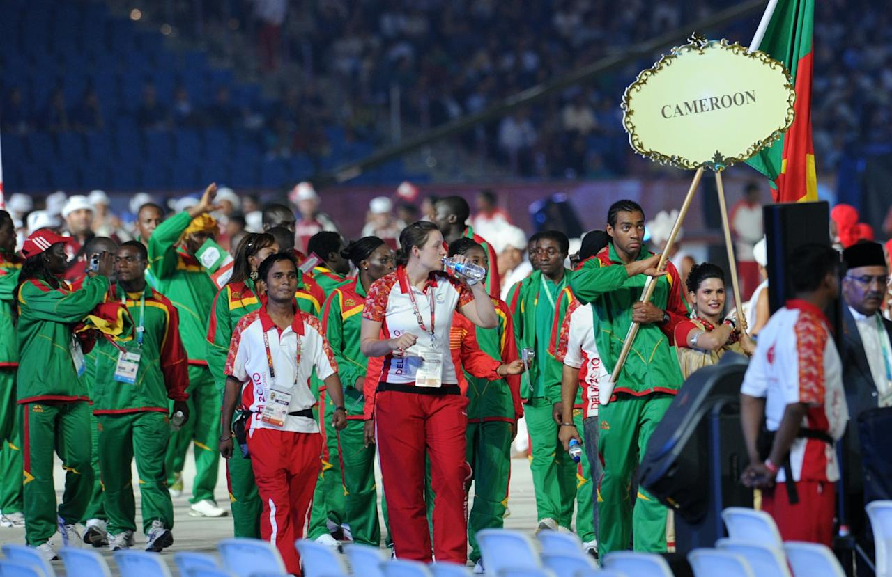 Cameroon athletes led by flag bearer Hugo Mamba (R) take part in the opening ceremony of the XIX Commonwealth Games in New Delhi on October 3, 2010.   The 2010 Commonwealth Games ceremony started in New Delhi with a near-capacity 60,000 crowd rapturously applauding the opening laser display. Prince Charles, the Prince of Wales, and his wife Camilla, Duchess of Cornwall, were introduced to the Jawaharlal Nehru Stadium along with Indian President Prathiba Patil and Prime Minister Manmohan Singh as the audience stood for the national anthem.    AFP PHOTO / PRAKASH SINGH (Photo credit should read PRAKASH SINGH/AFP/Getty Images)