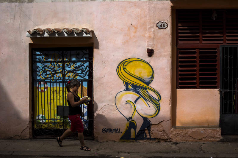 A woman passes by a closed art store decorated by a mural in Havana, Cuba, Wednesday, Dec. 5, 2018. After weeks of public debates and overlapping complaints from artists and intellectuals about a decree that increased control for artists and promoters, Cuban authorities are about to publicize complementary rules that limit the power of cultural inspectors and limit official action about creation. (AP Photo/Desmond Boylan)