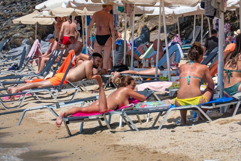 A woman suntans topless on a beach in Europe. Source: Getty