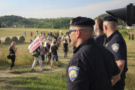 Croatian police officers stand as people walk with banners during a protest against the violent pushbacks of migrants, allegedly conducted by Croatian police, near the border crossing between Croatia and Bosnia Herzegovina in Maljevac, Croatia, Saturday, June 19, 2021. More than one hundred members of human rights NGO's, mostly from Italy, but also from Germany, Austria, Spain and Slovenia blocked the border traffic for about two hours protesting demanding a stop of all deportation of migrants, and cancellation of EU's Frontex operations at borders, preventing migrants from traveling. (AP Photo/Edo Zulic)