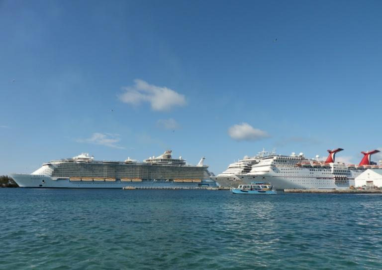 The Royal Caribbean ship Allure of the Seas (L) and Carnival Cruise ships Liberty and Elation are seen in Nassau, Bahamas in April 2019 (AFP Photo/Daniel SLIM)