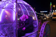 Members of the public pose for a picture as they visit Blackpool's annual Illuminations in Blackpool, England, Wednesday Nov. 4, 2020, before being switched off at midnight on Wednesday due to the lockdown. Britain is preparing to join large swathes of Europe in a coronavirus lockdown designed to save its health care system from being overwhelmed. Pubs, along with restaurants, hairdressers and shops selling non-essential items will have to close Thursday until at least Dec. 2. (AP Photo/Jon Super)