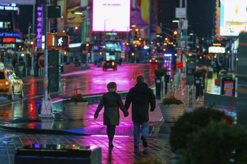 A couple walks through Times Square in the early morning Sunday, Jan. 20, 2019, in New York. The National Weather Service said on Saturday that a dramatic drop in temperatures could turn the weekend's rainfall into ice before Monday. (AP Photo/Kevin Hagen)