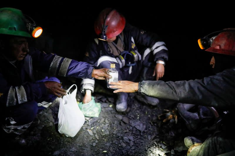 Artisanal gold miners drink anise and chew coca leaves as part of a ritual before starting work in a mine in La Rinconada, in the Andes
