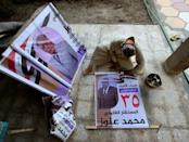 An Iraqi independent candidate prepares to hang his own electoral poster on October 6 in the central city of Najaf (AFP/Ali NAJAFI)
