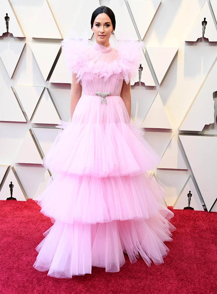 "<p>Wearing a <a href=""https://www.popsugar.com/fashion/Kacey-Musgraves-Dress-2019-Oscars-45832037"" class=""ga-track"" data-ga-category=""Related"" data-ga-label=""https://www.popsugar.com/fashion/Kacey-Musgraves-Dress-2019-Oscars-45832037"" data-ga-action=""In-Line Links"">pink ruffled Giambattista Valli gown</a>.</p>"