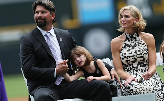 From left, retired Colorado Rockies first baseman Todd Helton sits with his youngest daughter, Gentry Grace, and wife Christy during a ceremony to retire the player's number before the Rockies host the Cincinnati Reds in a baseball game in Denver on Sunday, Aug. 17, 2014. (AP Photo/David Zalubowski)