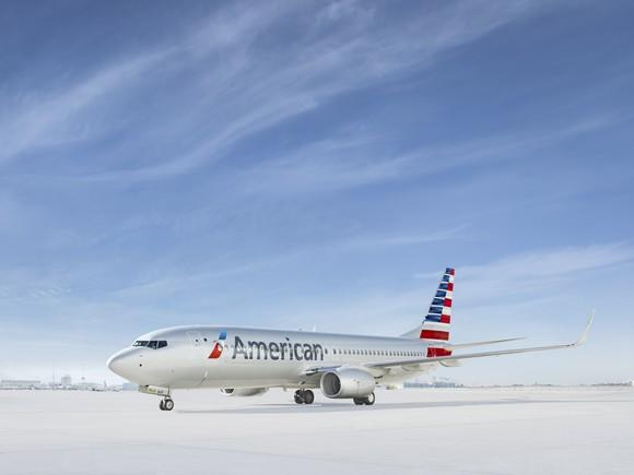 An American jet sits on an open runway.