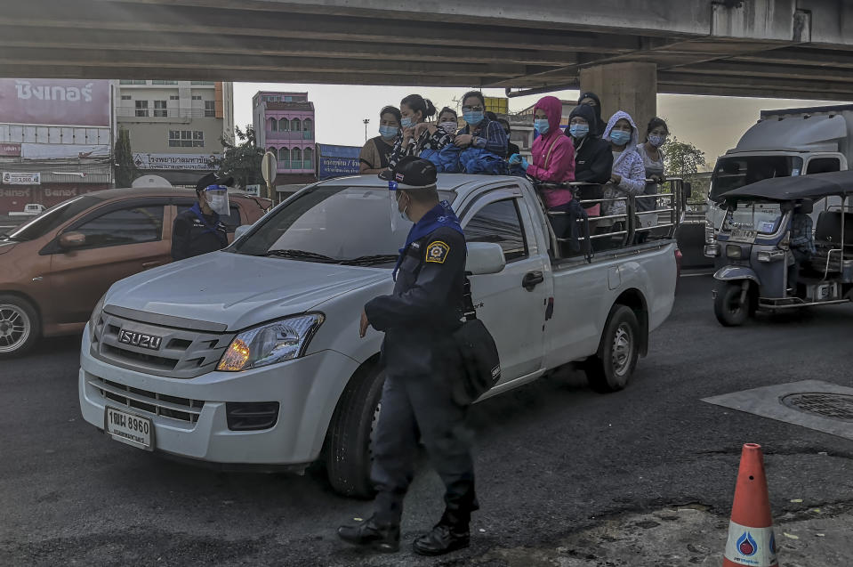 A group of migrant workers arrive in a back of a truck to get screened for COVID-19 in Samut Sakhon, South of Bangkok, Thailand, Sunday, Dec. 20, 2020. Thailand reported more than 500 new coronavirus cases on Saturday, the highest daily tally in a country that had largely brought the pandemic under control. (AP Photo/ Chalida Ekvitthayavechnukul)