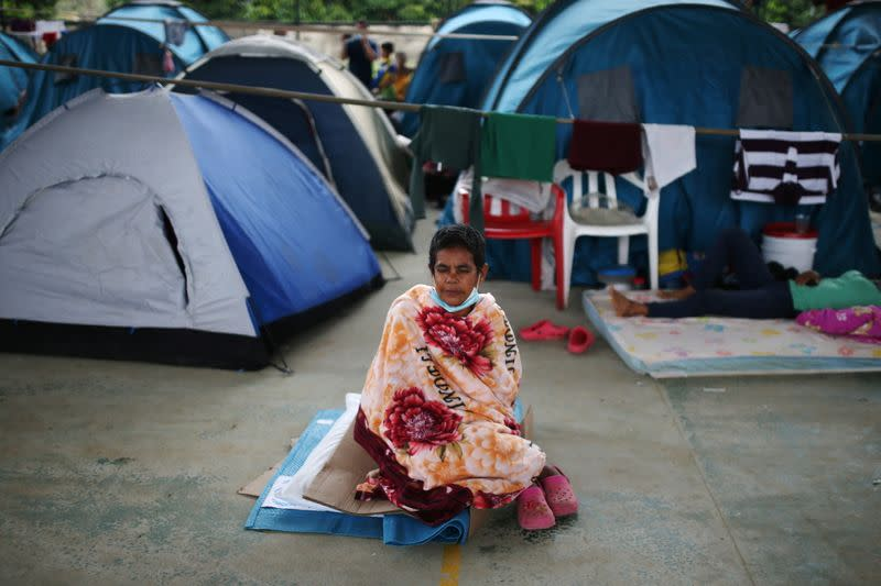 A Venezuelan migrant rests on a pillow inside a coliseum where a temporary camp has been set up, after fleeing her country due to military operations, according to the Colombian migration agency, in Arauquita