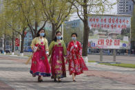 "Women walk in a street near the Arch of Triumph on the Day of the Sun, the birth anniversary of late leader Kim Il Sung, in Pyongyang, North Korea Thursday, April 15, 2021. The poster reads ""The great leader Comrade Kim Il Sung will always be with us. Day of the Sun."" (AP Photo/Cha Song Ho)"