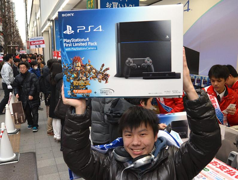 A customer holds up a Sony PlayStation 4 video game console after buying it in Tokyo on February 22, 2014 (AFP Photo/Kazuhiro Nogi)