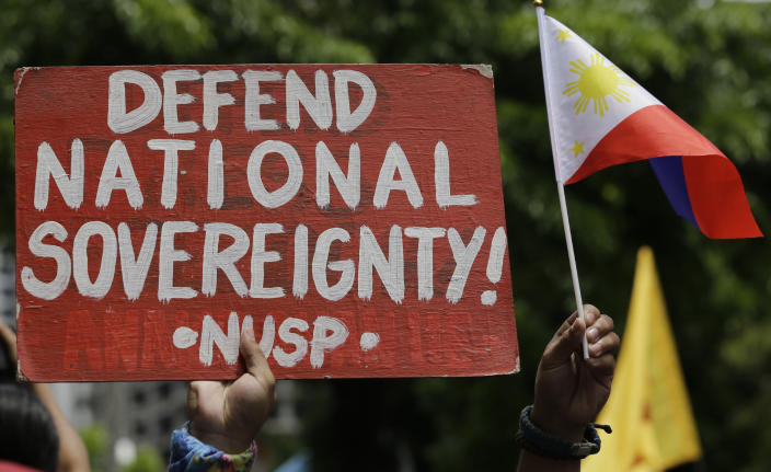 A protester holds a slogan during a rally outside the Chinese Consulate in the financial district of Makati, metropolitan Manila, Philippines to mark Independence Day on Wednesday, June 12, 2019. The Philippine defense secretary says an anchored Filipino fishing boat has sunk in the disputed South China Sea after being hit by a suspected Chinese vessel which then abandoned the 22 Filipino crewmen. (AP Photo/Aaron Favila)