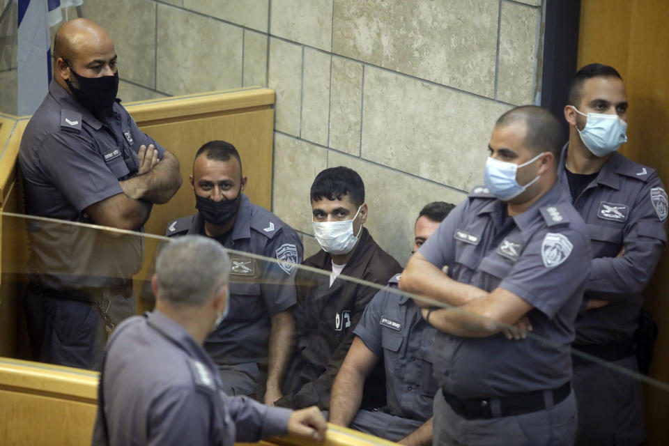 CORRECTS NAME, Mahmoud Aradeh is surrounded by guards as they stand in a courtroom in Nazareth, Israel, after he and three other Palestinian fugitives were captured on Saturday, Sept. 11, 2021. Israeli police on Saturday said they have arrested four of the six Palestinians who broke out of a maximum-security prison this week including a famed militant leader whose exploits over the years have made him a well-known figure in Israel. (AP Photo/Sebastian Scheiner)