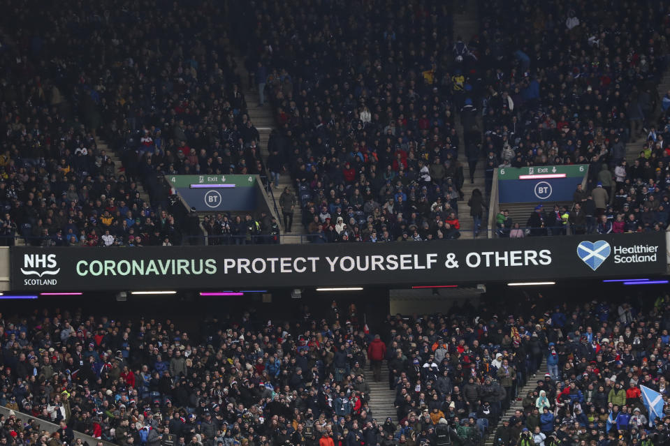"""A message that reads: """"Coronavirus protect yourself and others"""" is displayed during the Six Nations rugby union international match between Scotland and France at the Murrayfield stadium in Edinburgh, Scotland, Sunday, March 8, 2020. (AP Photo/Scott Heppell)"""