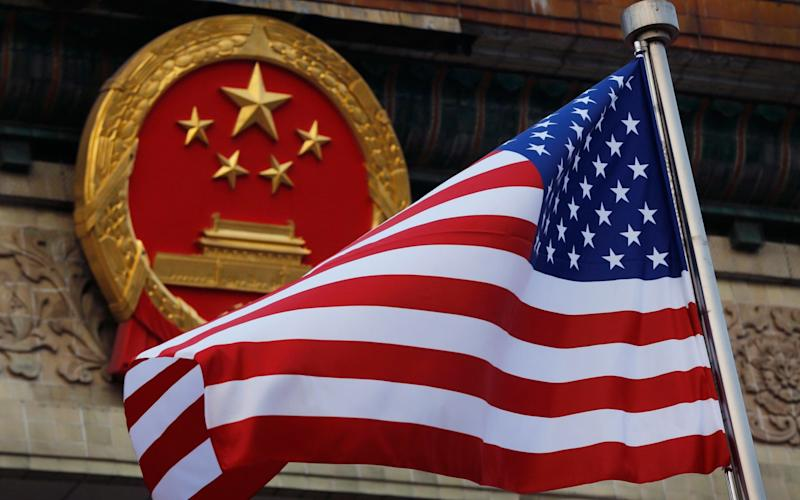 An American flag is flown next to the Chinese national emblem during a welcome ceremony for visiting U.S. President Donald Trump - AP