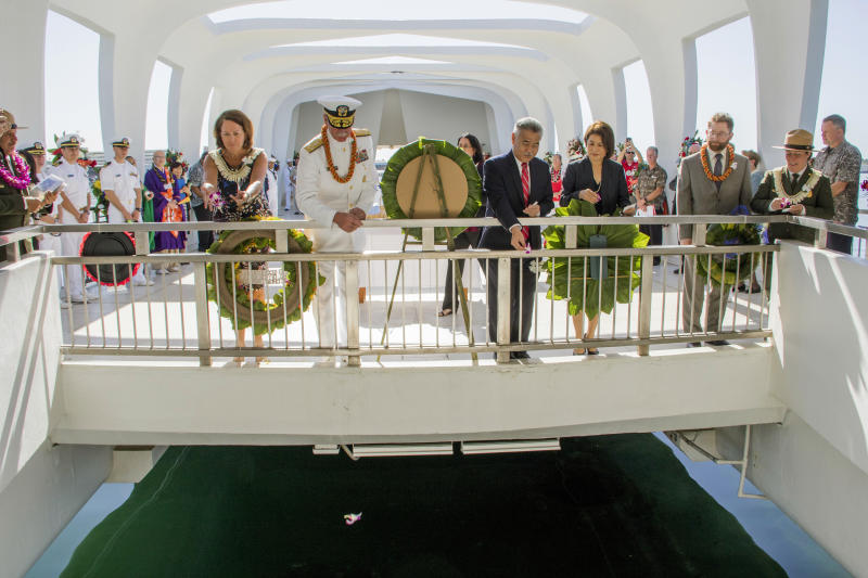 ADDS DATE OF DEC. 7, 2017- Adm. Scott Swift, left center, along with his wife and Gov. David Ige, right center, and his wife Dawn Amano Ige throw orchids into the waters of the Arizona Memorial in Honolulu, during a ceremony commemorating the 76th anniversary of the attack on Pearl Harbor, Thursday, Dec. 7, 2017. (Dennis Oda /The Star-Advertiser via AP, Pool)