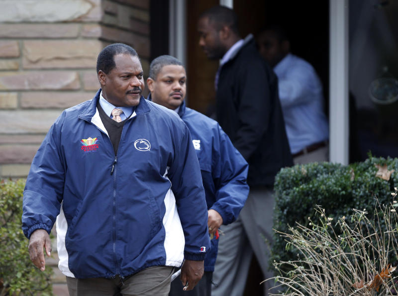 Assistant coach Larry Johnson, left, and others leave former Penn State football coach Joe Paterno's home Thursday, Nov. 10, 2011, in State College, Pa.  (AP Photo/Matt Rourke)