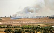 Smoke rises from an Israeli farming area after Palestinians flew a kite carrying a Molotov cocktail over the on border from Gaza on April 17, 2018