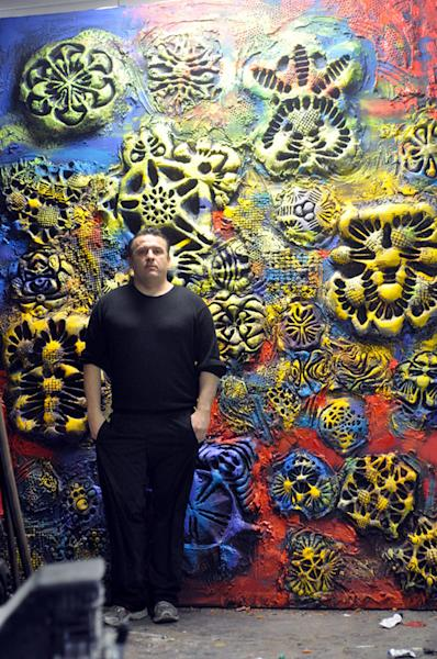 Artist Ioan Florea stands in front of one of his giant paintings created using 3D-printing techniques that give the finished product both tactile and visual elements.