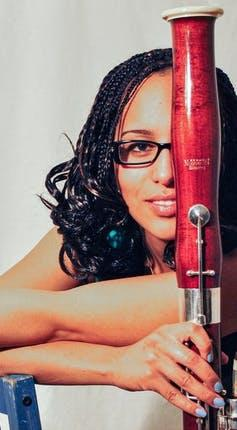 Side view of a Black woman in glasses holding a bassoon.