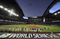 The Los Angeles Dodgers line up during during the national anthem and a fly over before Game 1 of the baseball World Series against the Tampa Bay Rays Tuesday, Oct. 20, 2020, in Arlington, Texas. (AP Photo/Eric Gay)