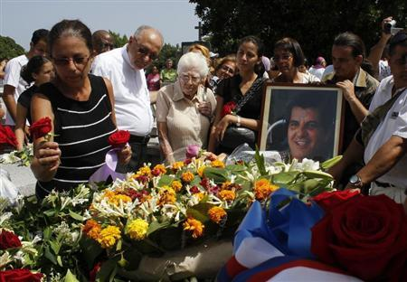 Ofelia Acevedo, wife of Oswaldo Paya, one of Cuba's best-known dissidents, places a rose on the tomb of her husband during his burial in Havana