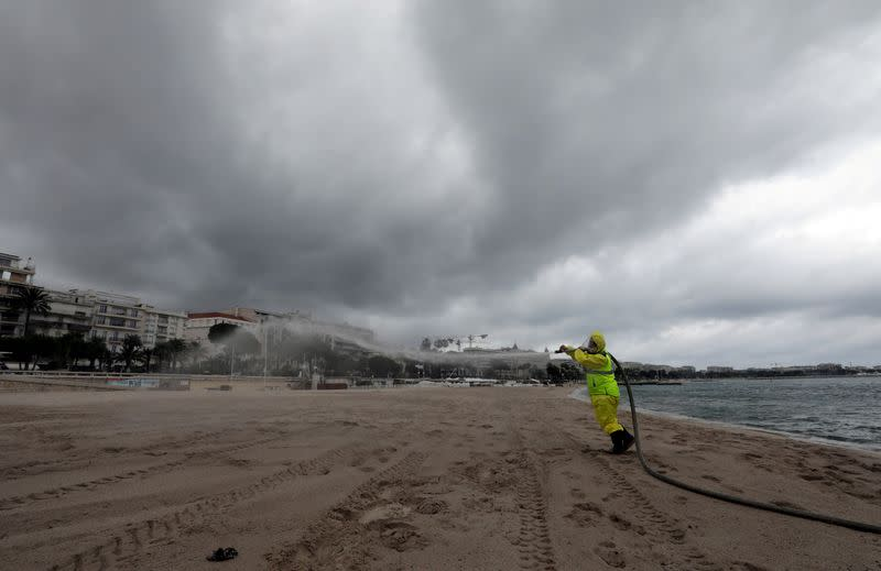 FILE PHOTO: A disinfection squad sprays disinfectant to clean beaches on the Croisette in Cannes