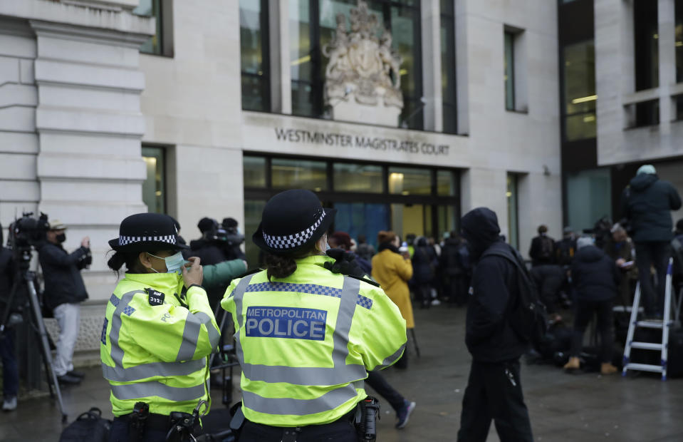 """Police officers look on as Julian Assange supporters and media gather outside Westminster Magistrates Court for his Bail hearing in London, Wednesday, Jan. 6, 2021. On Monday Judge Vanessa Baraitser ruled that Julian Assange cannot be extradited to the US. because of concerns about his mental health. Assange had been charged under the US's 1917 Espionage Act for """"unlawfully obtaining and disclosing classified documents related to the national defence"""". Assange remains in custody, the US. has 14 days to appeal against the ruling. (AP Photo/Matt Dunham)"""