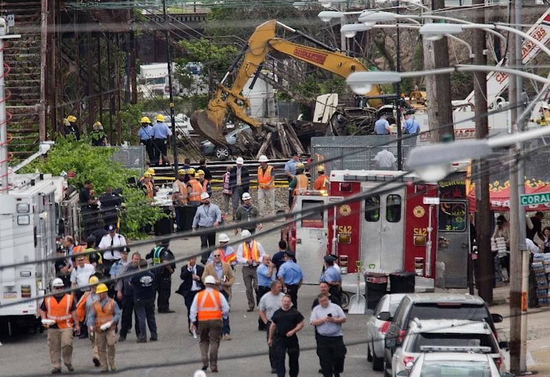 A crane clears wood beams from the track close to the wreckage of an Amtrak Northeast Regional Train in Philadelphia, Pennsylvania, on May 13, 2015 (AFP Photo/Andrew Caballero-Reynolds)