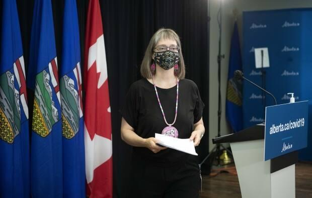 Dr. Deena Hinshaw, Alberta's chief medical officer of health, is seen leaving the podium after a June 29 news conference. Hinshaw's next media availability, almost one month later, was the announcement that testing, contract tracing and mandatory isolation would be scaled back. (Chris Schwarz/Government of Alberta - image credit)