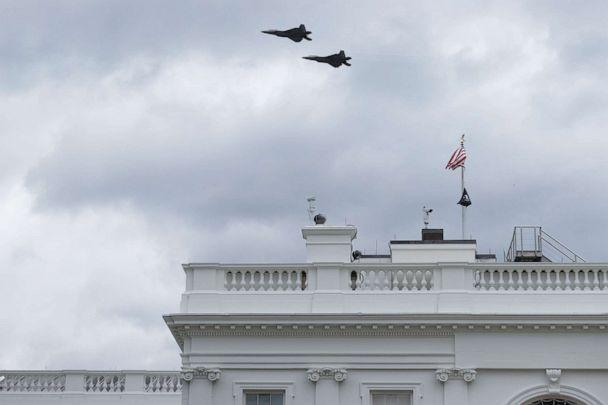PHOTO: Two military aircraft fly over the White House on April 16, 2021 in Washington, DC. The US Air Force F-22 fighter aircraft flew over Washington as part of the World War I memorial dedication ceremony. (Chip Somodevilla/Getty Images)