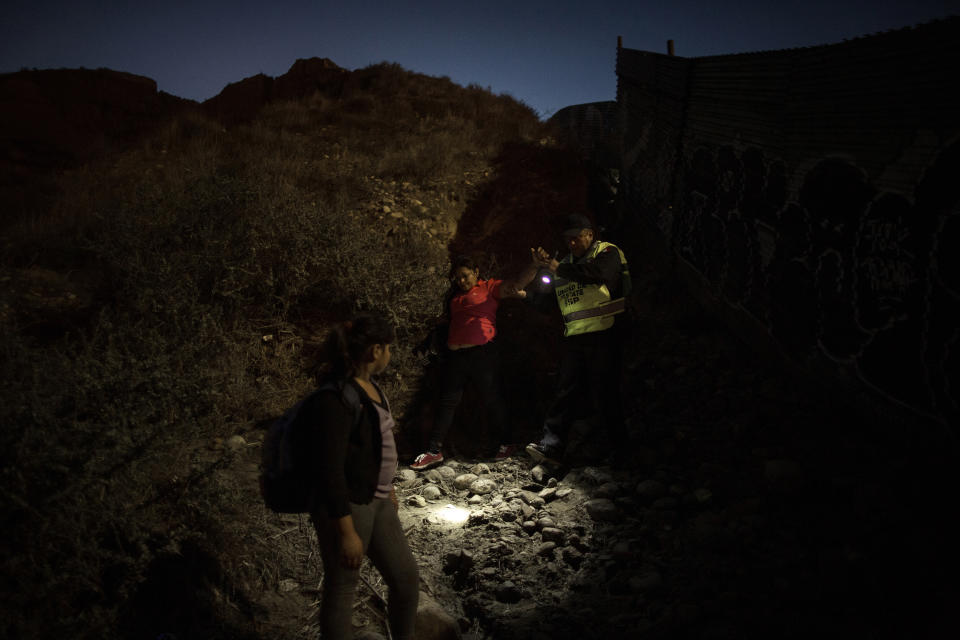 Mirna (43) and her daughter Mirna -Marely (10) both from Honduras, are caught by Mexican border police along the Mexico-US border wall on December 1, 2018.  (Photo: Fabio Bucciarelli for Yahoo News)