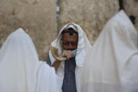 An ultra-Orthodox Jewish man blows a shofar, a musical instrument made from an animal horn, as he prays ahead of the Jewish new year at the Western Wall, the holiest site where Jews can pray in Jerusalem's old city, Wednesday, Sept. 16, 2020. A raging coronavirus outbreak is casting a shadow over the normally festive Jewish New Year. (AP Photo/Sebastian Scheiner)