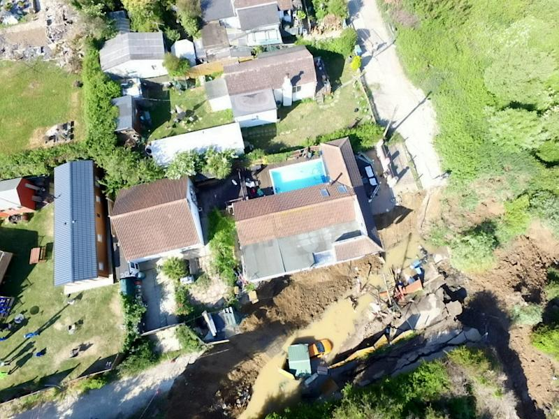 Shocking new photos show a house teetering on the edge of a cliff, after a dramatic collapse forced the evacuation of 20 houses in Eastchurch, Kent. May 31 2020. See SWNS story SWNNcliff. Shocking new photos show a house teetering on the edge of a cliff, after a dramatic collapse forced the evacuation of 20 houses. Drone footage shows a home - in Eastchurch, Kent - hanging off the edge off the cliff, with cars also tumbling down the slope. Up to three metres of land in front of the property fell away on Friday night after years of erosion. While all but two of the households were able to return home yesterday, several were left without electricity as a result of the incident - and one is at serious risk of collapsing into the sea.