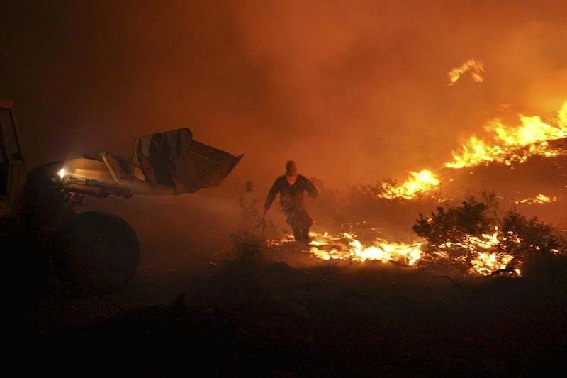 In this Sunday, Aug. 19, 2012 photo, a man holding a makeshift fire broom takes part in efforts to contain a major forest blaze on the Greek eastern Aegean Sea island of Chios. Hundreds of firefighters, soldiers and volunteers were struggling for a third day Monday to tame a fire that burnt some 7,000 hectares of forest, cultivated land and groves of the island's famed mastic trees. Smoke from the blaze, which was swept on by gale-force winds, was carried as far as the southern island of Crete, more than 350 kilometers (230 miles) away. (AP Photo/Icon Press) GREECE OUT