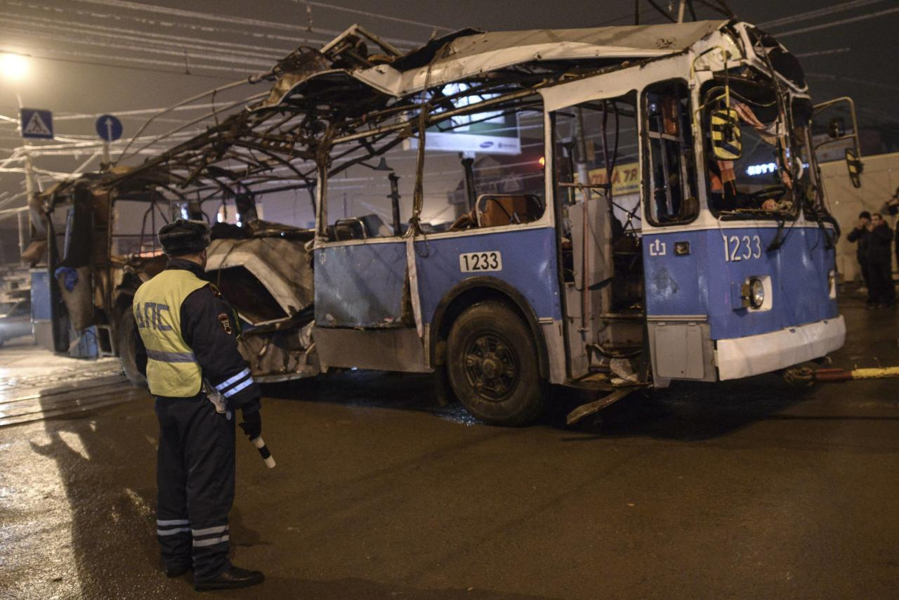 A policeman watches as a bus, destroyed in an earlier explosion, is towed away in Volgograd December 30, 2013. A bomb ripped apart a bus in Volgograd on Monday, killing 14 people in the second deadly attack blamed on suicide bombers in the southern Russian city in 24 hours and raising fears of Islamist attacks on the Winter Olympics. REUTERS/Sergei Karpov (RUSSIA - Tags: CIVIL UNREST CRIME LAW DISASTER TRANSPORT)