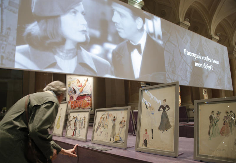 """Visitors look at the """"Paris Vu par Hollywood"""" exhibition at Paris City hall during the presentation in Paris, Monday, Sept, 17, 2012. A new exhibit, """"Paris seen by Hollywood"""" opens its doors in the city of light. It explores the silver screen's enduring fascination with Paris featuring clips and images tracing several decades of cinema history;from silent film all the way up to 1990's action movies. (AP Photo/Francois Mori)"""