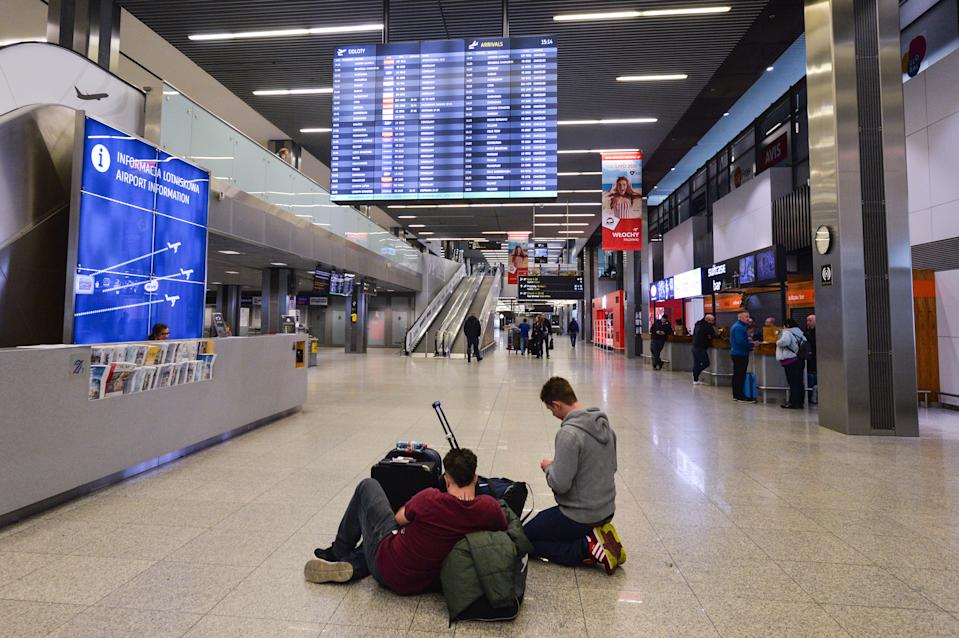 Young foreign passengers awaiting for their 'rescue flights' inside the Terminal Hall of John Paul II Krakow-Balice International Airport. With a total of 119 confirmed cases of coronavirus and three people dead, Poland declared a state of epidemic emergency and closure of its borders. From March 15, all international flights for passenger traffic were suspended. However, a few KLM or EasyJet rescue flights were allowed to land at Krakow airport to pick up foreign passengers On Sunday, March 15, 2020, in John Paul II Krakow-Balice International Airport, Krakow, Poland. (Photo by Artur Widak/NurPhoto via Getty Images)