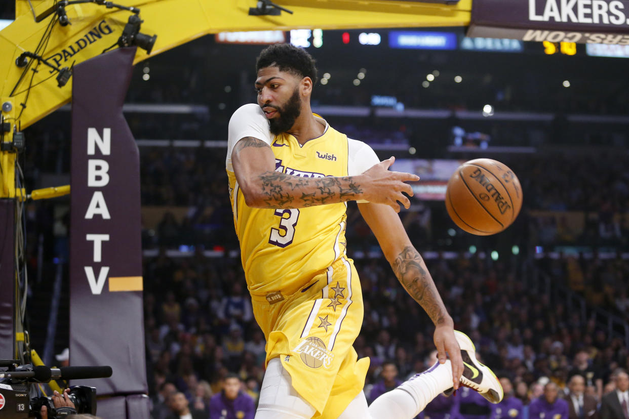 Los Angeles Lakers' Anthony Davis keeps the ball in play during the first half of the team's NBA basketball game against the Los Angeles Clippers, Wednesday, Dec. 25, 2019, in Los Angeles. (AP Photo/Ringo H.W. Chiu)