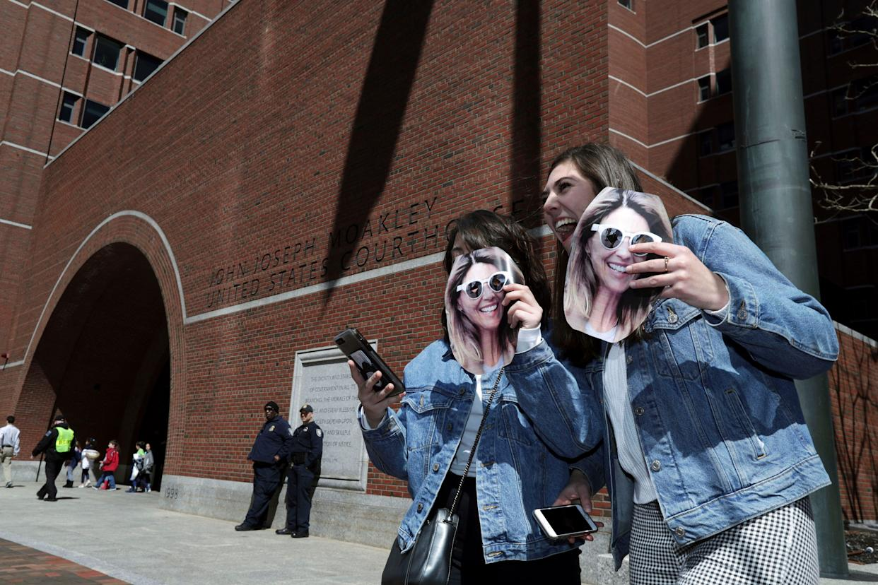Two fans of actress Lori Loughlin hold cutout photos of her outside federal court in Boston where Loughlin is scheduled to face charges in a nationwide college admissions bribery scandal, on April 3, 2019.