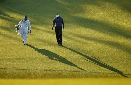FILE PHOTO: Vijay Singh of Fiji casts a shadow as he walks up the first fairway with his caddie Cayce Kerr during first round play of the Masters golf tournament at the Augusta National Golf Course in Augusta, Georgia April 9, 2015. REUTERS/Brian Snyder/File Photo