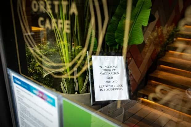 A sign reminding patrons of a mandatory vaccination policy for indoor-dining is pictured in a Toronto cafe on Sept. 22, 2021. As last month, patrons of dine-in restaurants, nightclubs, gyms, sports facilities and other venues have been required to present a receipt of full vaccination along with government identification. (Evan Mitsui/CBC - image credit)