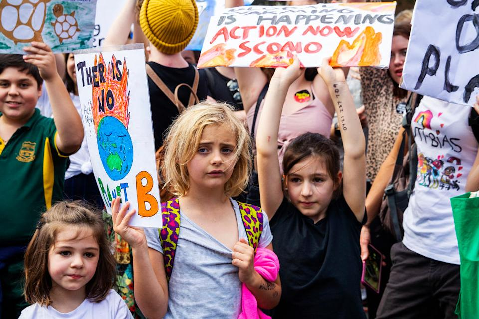 Children holding up signs during a climate strike rally outside Parliament House.