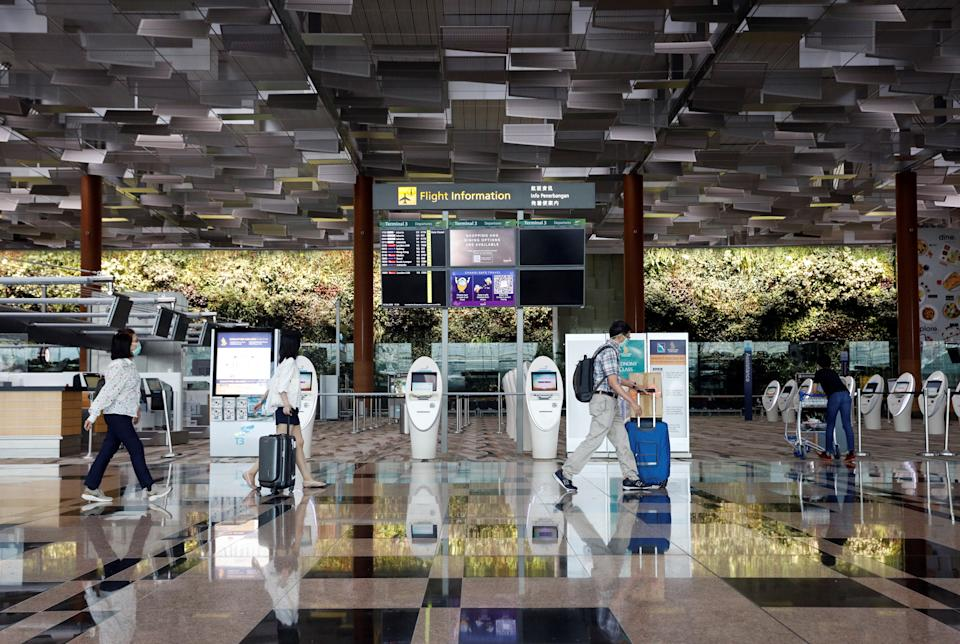 People wearing protective face masks walk past self check-in machines, amid the spread of the coronavirus disease (COVID-19) at the Changi Airport in Singapore October 12, 2020. REUTERS/Edgar Su