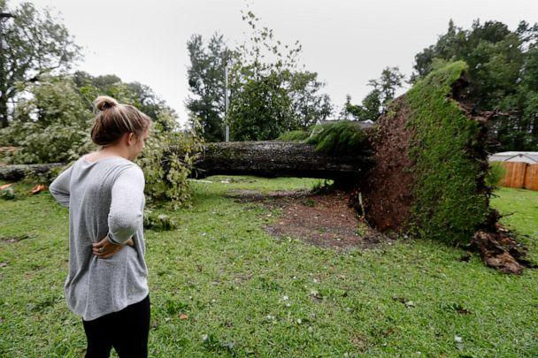 PHOTO: Kelsey Myers looks at an overturned tree in her front yard in Summerville, S.C., after Hurricane Dorian passed by, Sept. 5, 2019, in Summerville, S.C. (Mic Smith/AP)