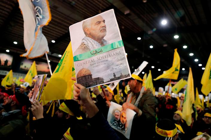 A supporter of Shiite Hezbollah movement holds a poster of slain Iranian Major General Qasem Soleimani as the movement's leader delivers a speech on a screen in the Lebanese capital Beirut's southern suburbs on January 5, 2020.